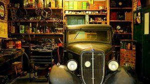A garage with an old car and a lot of tools. During a move, it will not be easy to pack your garage because it is not clutter-free.